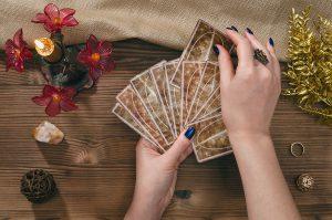 Cartes de tarot et mains de diseuse de bonne aventure sur fond de table en bois.