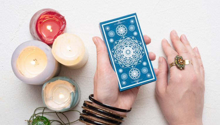 hand holding a deck of tarot cards