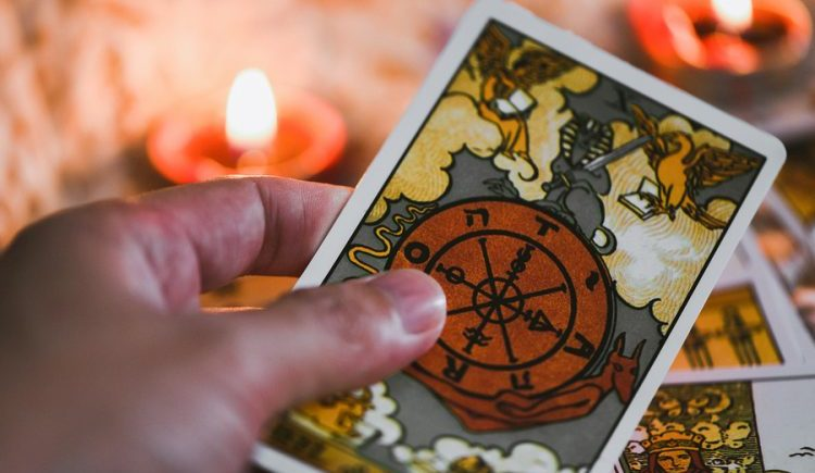 Tarot Cards In Hand For Tarot Reading With Candlelight Backgroun